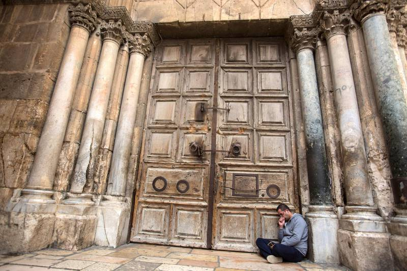 A Palestinian Christian named Nidal Aboud, 24, from the Old City of Jerusalem sits on the ground against the gigantic wooden doors of the  Church of the Holy Sepulchre in the Old City of Jerusalem on Monday February 26,2018.The Church of the Holy Sepulchre  remained closed for a second day after church leaders in Jerusalem closed it to protest against Israeli's announced plans by the cityÕs municipality earlier this month to collect property tax (arnona) from church-owned properties on which there are no houses of worship. Nadal said he was in mourning for the state of Christians in the Holy Land and said he never in his life saw the church closed before . (Photo by Heidi Levine for The National).
