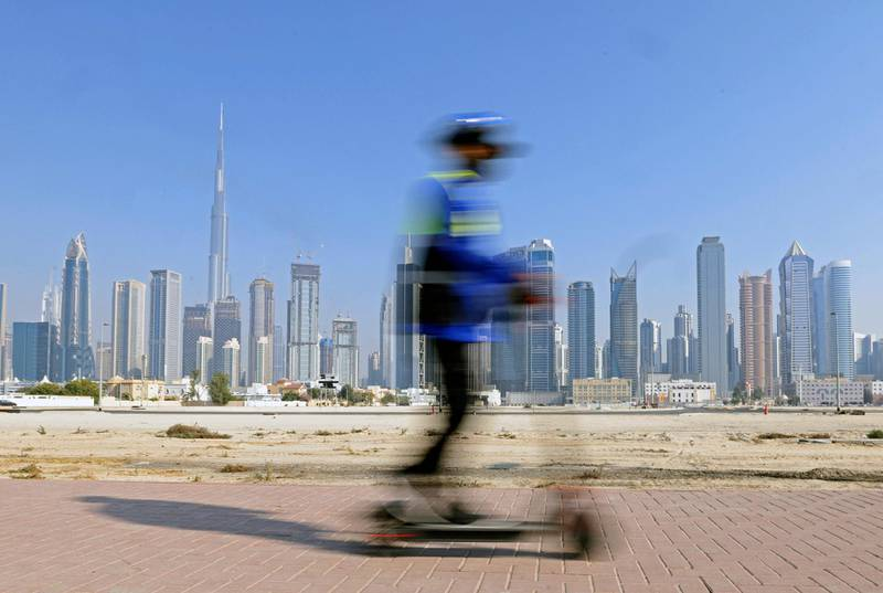 A man rides his electric scooter in Dubai backdropped by the Gulf emirate's highrise buildings on February 16, 2021.  / AFP / Karim SAHIB