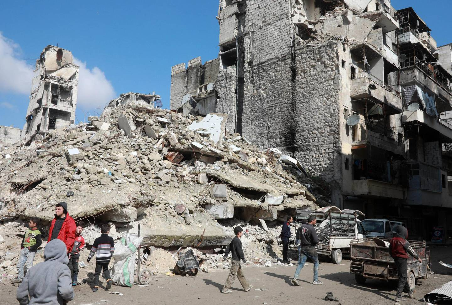 People walk past the rubble of buildings that were heavily damaged or destroyed during battles between rebel fighters and regime forces, in the former opposition-held district of Salaheddin in the northern Syrian city of Aleppo on February 11, 2019. (Photo by LOUAI BESHARA / AFP)