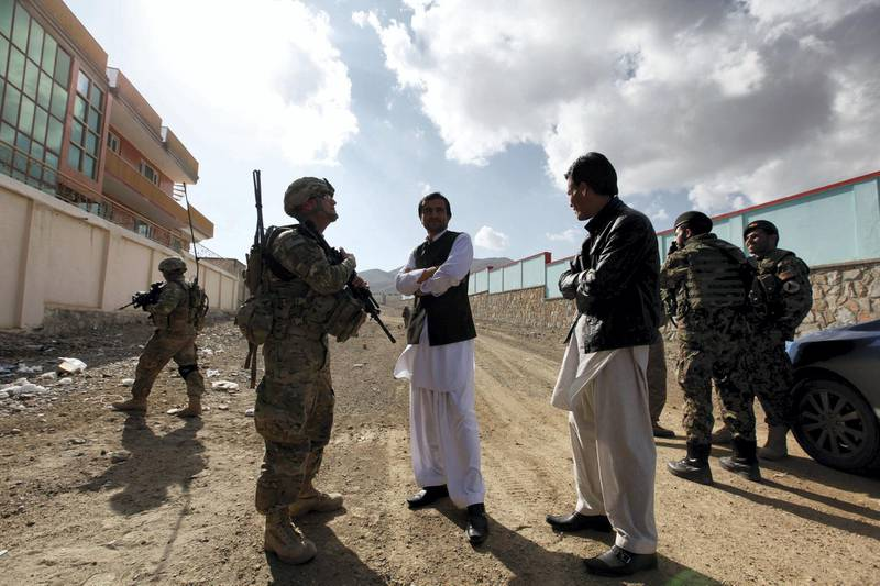 Afghan residents chat with U.S. Army Lieutenant Steven Gibbs of the PSD 3/1AD Special Troops Battalion as he patrols with his platoon in Pul-e Alam, a town in Logar province, eastern Afghanistan November 28, 2011. REUTERS/Umit Bektas (AFGHANISTAN - Tags: POLITICS MILITARY)