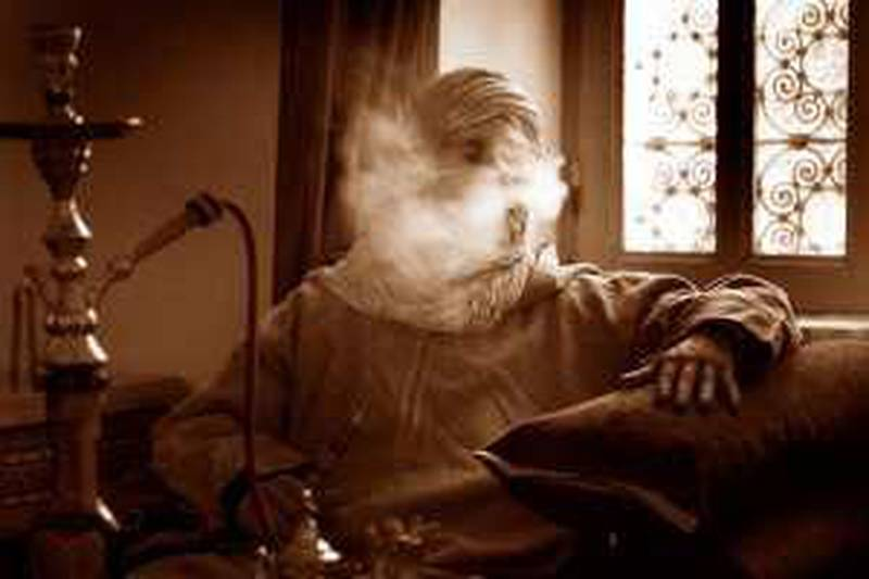 Mature man with hookah pipe blowing out smoke (B&W)