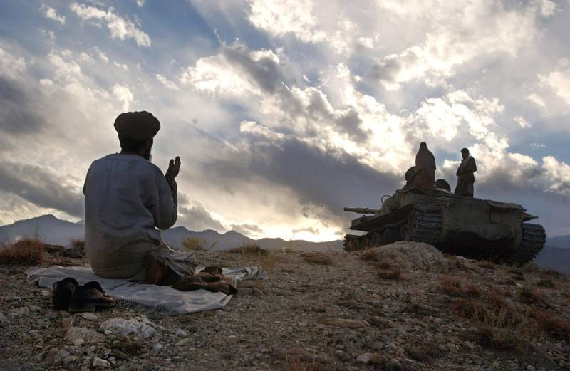 398395 02: An anti-Taliban soldier prays near a tank December 10, 2001 on the hills overlooking the Tora Bora area of Afghanistan. Anti-Taliban soldiers bombed and fought hand to hand with al Qaeda fighters in an attempt to oust the estimated 2,000 soldiers loyal to Osama bin Laden that are holed up in caves in the rugged countryside. (Photo by Chris Hondros/Getty Images)