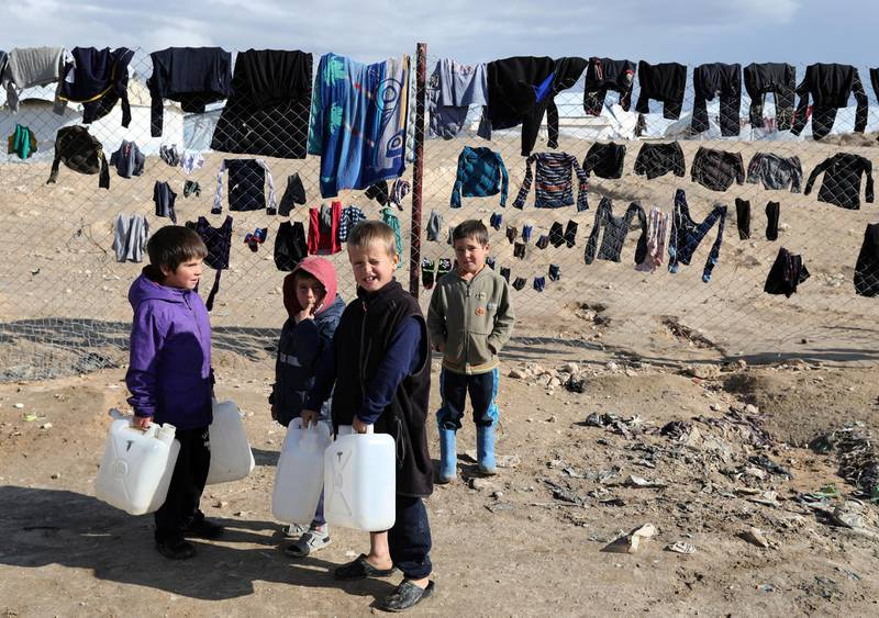 """Children hold onto water containers in al-Hol camp, Syria, January 8, 2020. REUTERS/Goran Tomasevic     SEARCH """"ISLAMIC STATE PRISONERS"""" FOR THIS STORY. SEARCH """"WIDER IMAGE"""" FOR ALL STORIES."""
