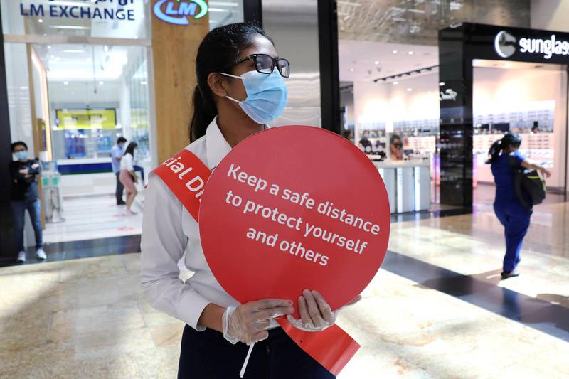 FILE PHOTO: A woman wearing a protective face mask and gloves holds a sign at Mall of the Emirates after the UAE government eased a curfew and allowed stores to reopen following the outbreak of the coronavirus disease (COVID-19) in Dubai, United Arab Emirates, May 5, 2020. REUTERS/Ahmed Jadallah/File Photo