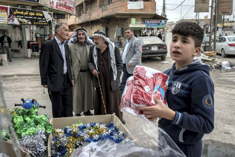 A boy sets out Christmas decorations at a shop in Qaraqosh, Iraq, 20 December 2017.