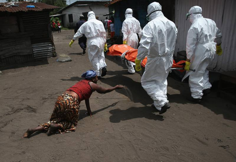 MONROVIA, LIBERIA - OCTOBER 10:  A woman throws a handful of soil towards the body of her sister as Ebola burial team members take her sister Mekie Nagbe, 28, for cremation on October 10, 2014 in Monrovia, Liberia. Nagbe, a market vendor, collapsed and died outside her home earlier in the morning while leaving to walk to a treatment center, according to her relatives. The burial of loved ones is important in Liberian culture, making the removal of infected bodies for cremation all the more traumatic for surviving family members. The World Health Organization says the Ebola epidemic has now killed more than 4,000 people in West Africa. (Photo by John Moore/Getty Images)