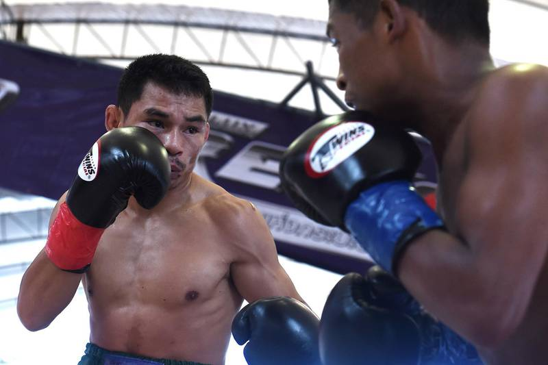"""Thai boxer Wanheng Menayothin (L) aims a blow against Panamanian challenger Leroy Estrada (R) to win his 50th straight victory on May 2, 2018 in Nakhon Ratchasima and retain his WBC title.     The 32-year-old Thai nicknamed the """"dwarf giant"""" reached the milestone in the fifth round of the minimumweight championship bout against Leroy Estrada in the northeastern Thai city of Nakhon Ratchasima. / AFP PHOTO / LILLIAN SUWANRUMPHA"""