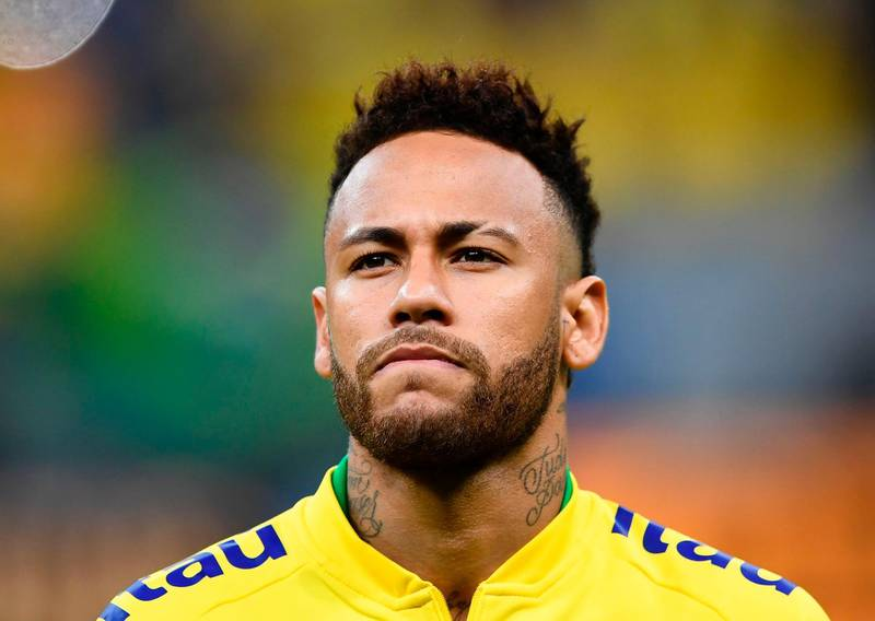 """(FILES) In this file photo taken on June 06, 2019 Brazil's Neymar warms up before a friendly football match against Qatar at the Mane Garrincha stadium in Brasilia ahead of Brazil 2019 Copa America. Neymar is ready to cut his salary by 12 million euros to leave Paris Saint-Germain as part of a """"verbal agreement"""" reached between the Brazilian and Barcelona, according to reports in the Spanish press released on June 25, 2019.  / AFP / EVARISTO SA"""