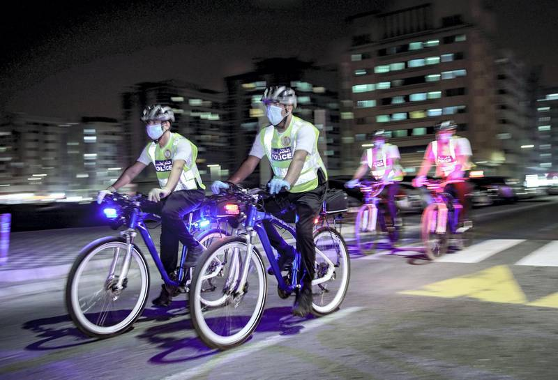 Abu Dhabi, United Arab Emirates, May 11, 2020.   Abu Dhabi Police bicycle patrol do night operations around the Mussaffah area to warn or catch curfew violators in the residential areas. --  Police officers start the nighttime operations.Victor Besa / The NationalSection:  NAReporter:  Haneen Dajani