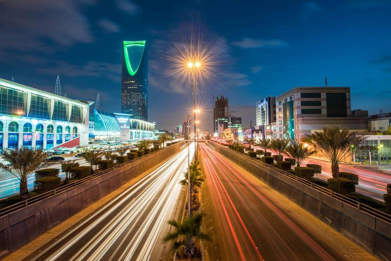 The Kingdom Tower, operated by Kingdom Holding Co., left, stands alongside the King Fahd highway, illuminated by the light trails of passing traffic, in Riyadh, Saudi Arabia, on Saturday, Jan. 9, 2016. Saudi Arabian stocks led Gulf Arab markets lower after oil extended its slump from the lowest close since 2004. Photographer: Waseem Obaidi/Bloomberg
