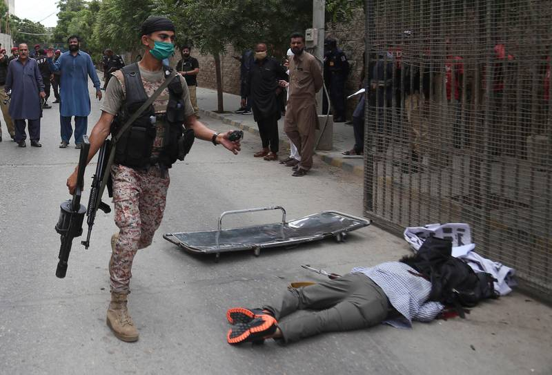 epa08515327 The body of a gunmen at the scene of an attack by unknown gunmen at Karachi Stock Exchange in Karachi, Pakistan, 29 June 2020. At least four gunmen and two civilians were reportedly killed and security forces have cordoned off the area as fighting is currently ongoing.  EPA/REHAN KHAN