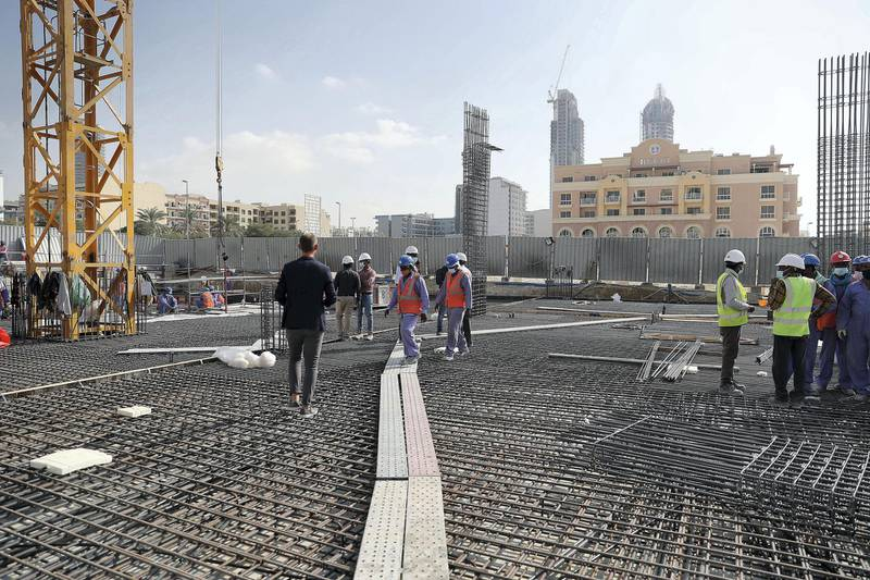 DUBAI, UNITED ARAB EMIRATES , Jan 31 – Labourers working at the site of co-living apartment block at the Jumeirah Village Circle in Dubai. (Pawan Singh / The National) For News/Online. Story by Georgia Tolley