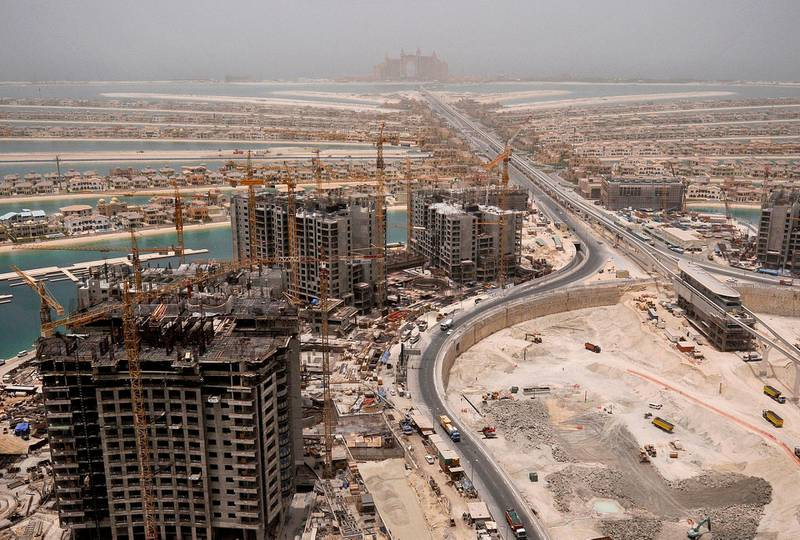 Cranes are seen on buildings currently under construction, on the Palm Jumeirah, as Atlantis, The Palm (top C) is seen on the breakwater of the Palm in Dubai, May 3, 2008.  REUTERS/Jumana El Heloueh (UNITED ARAB EMIRATES)