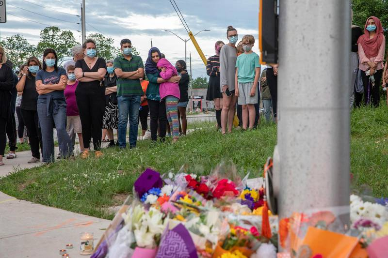 People attend at a memorial at the location where a family of five was hit by a driver, in London, Ontario, Monday, June 7, 2021. Four of the members of the family died and one is in critical condition. A 20-year-old male has been charged with four counts of first degree murder and count of attempted murder in connection with the crime. (Brett Gundlock/The Canadian Press via AP)