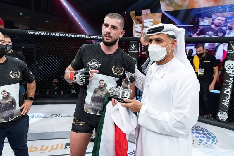 Mohammad Osseili receives the winner's prize from Abdulmunam Al Hashemi, chairman of Palms Sports. Courtesy UAE Warriors