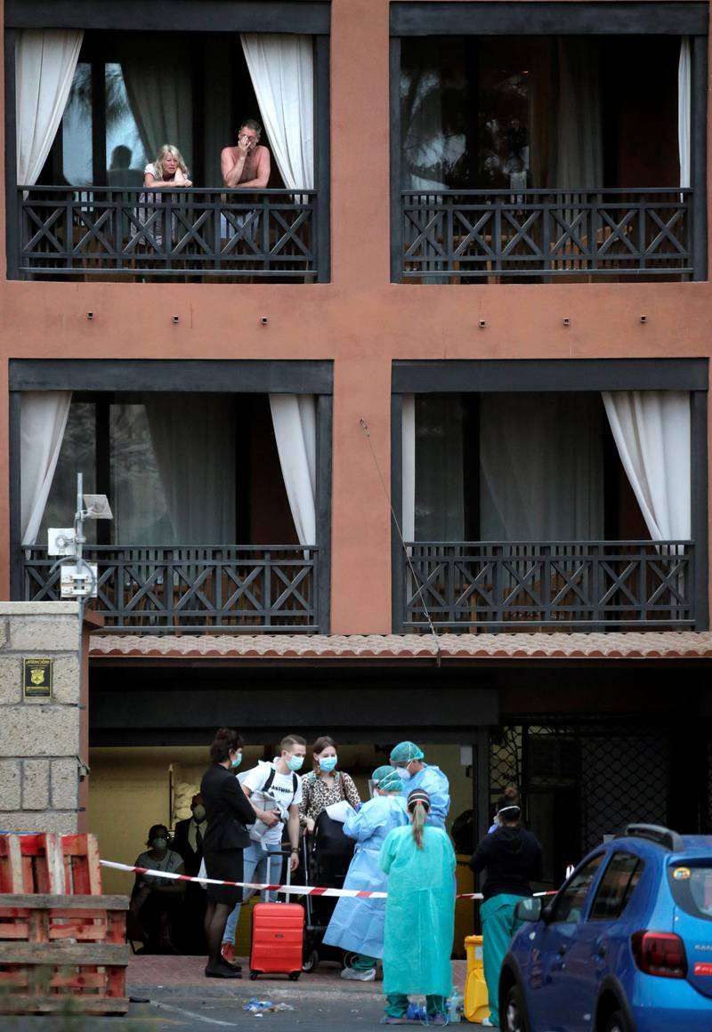 Health personnel wearing protection clothing check the temperature of a guest at the H10 Costa Adeje Palace hotel in La Caleta, in the Canary Island of Tenerife, Spain, Friday Feb. 28, 2020. Some guests have started to leave the locked down hotel after undergoing screening for the new virus that is infecting hundreds worldwide. (AP Photo/Joan Mateu)