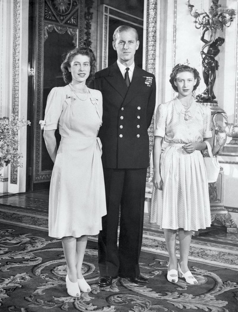 Princess Elizabeth, heiress presumptive to the throne, pictured in the White Drawing Room at Buckingham Palace with her husband to be, Lieut. Philip Mountbatten and her sister Princess Margaret.