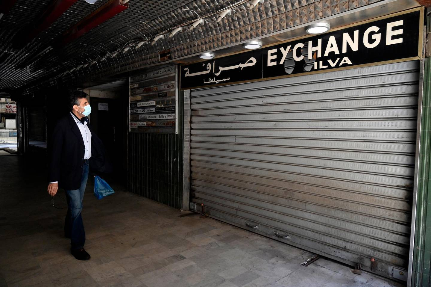 epa09079730 A man walks in front of a closed currency exchange shop at Hamra street in Beirut, Lebanon, 17 March 2021. The Lebanese pounds was exchanging at around 14,500 to the US dollar after the Lebanese pound has lost more than 85 percent of its value against the dollar on the black market in the worst economic crisis in Lebanon.  EPA/WAEL HAMZEH