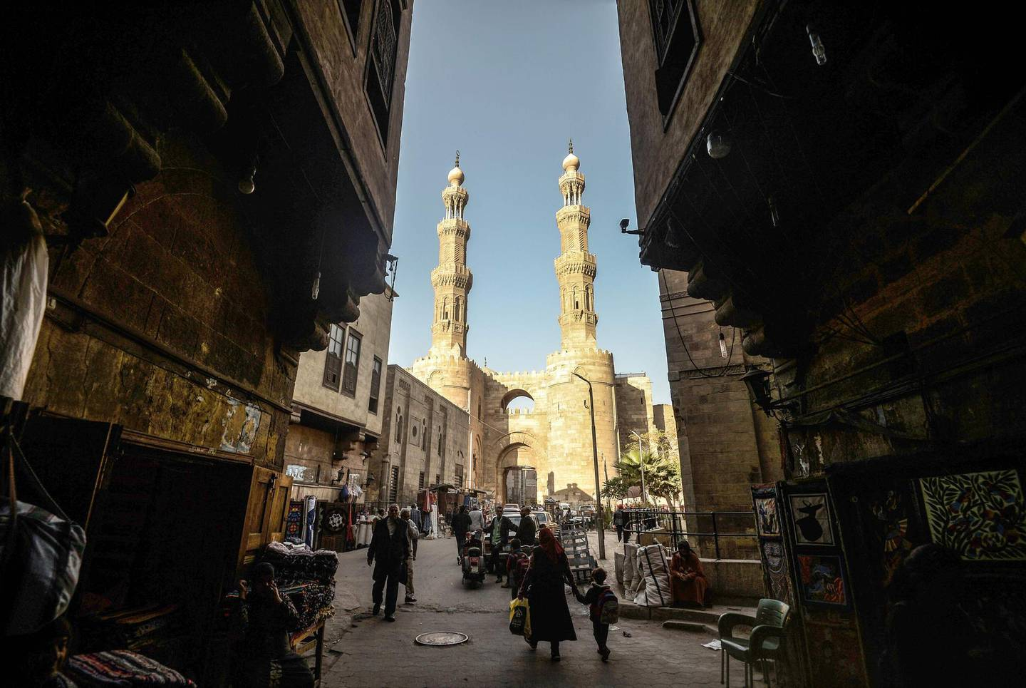 This picture taken on December 18, 2018 shows a view from the entrance of Khayamiya Street, or the Street of Tent-makers, leading up to the 11th century Bab Zuweila, one of the surviving main gates of the old city of the Egyptian capital Cairo. Along the sides of the roofed street of Khayamiya, or the Street of Tent-makers, dozens of craftsmen's shops have drawn foreign visitors for years until the 2011 uprising toppled longtime ruler Hosni Mubarak after which business has slowed to a trickle. The centuries-old art of Khayamiya, belived to have emerged during the Fatimid dynasty (10th-12th century AD), goes back to the time of travelling caravans, when huge tent pavilions were used as shields from the desert's searing sun. / AFP / Mohamed el-Shahed
