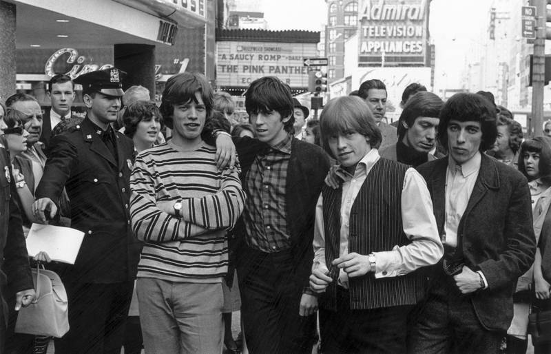 June 1964:  From left to right; Mick Jagger, Keith Richards, Brian Jones  (1942 - 1969), Charlie Watts and Bill Wyman of the Rolling Stones pose for a photo in a New York street, while a policeman holds back some curious spectators.  (Photo by William Lovelace/Express/Getty Images)