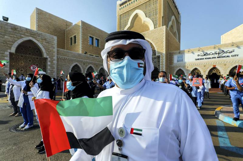 Abu Dhabi, United Arab Emirates, June 21, 2020.    Healthcare workers wave the UAE flag during the UAE Air Force's aerobatic display team, Al Fursan,  flies over Sheikh Khalifa Medical City, in an initiative of appreciation by the General Command of the UAE Armed Forces for the nation's medical teams and staff.Victor Besa  / The NationalSection:  NAReporter: