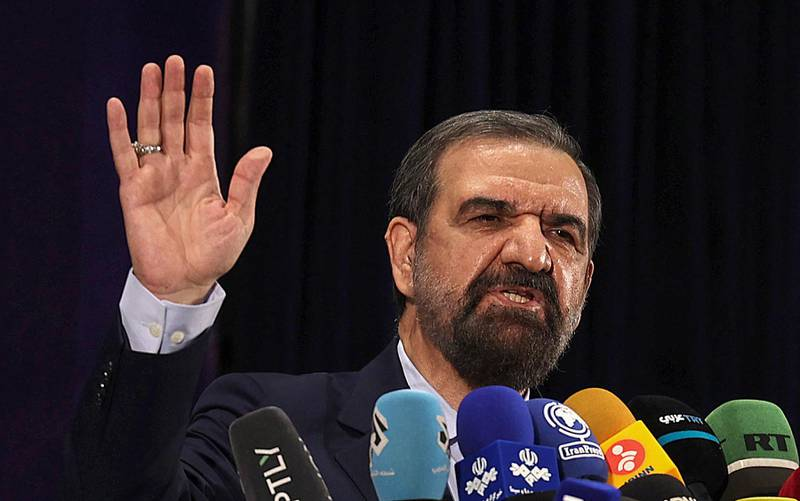 Iranian former chief of the Revolutionary Guards Mohsen Rezai talks to the media after registering his candidacy for the June presidential elections, at the Interior Ministry in the capital Tehran, on May 15, 2021. (Photo by ATTA KENARE / AFP)