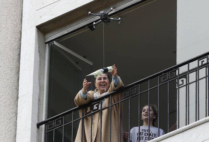 A woman standing on her balcony, reaches out to catch a rose delivered to her via a drone on Mother's day, in the Lebanese coastal city of Jounieh, north of the capital Beirut on March 21, 2020, as people remain indoors in an effort to limit the spread of the novel coronavirus. - In a quiet Lebanese town under lockdown over the novel coronavirus, a drone buzzed towards a balcony on Saturday to deliver a red rose to a mother grinning in surprise. The COVID-19 pandemic may have put a damper on Mother's Day this year, but three students have come up with a novel service to celebrate the occasion without flouting social distancing restrictions. (Photo by JOSEPH EID / AFP)