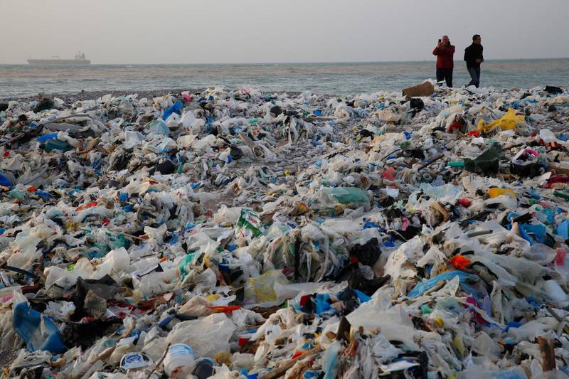 In this Monday, Jan. 22, 2018, photo, a man takes photos of piles of garbage washed on shore after an extended storm battered the Mediterranean country at the Zouq Mosbeh costal town, north of Beirut, Lebanon. Environmentalists say a winter storm has pushed a wave of trash onto the Lebanese shore outside Beirut, stirring outrage over a waste management crisis that has choked the country since 2015. (AP Photo/Hussein Malla)