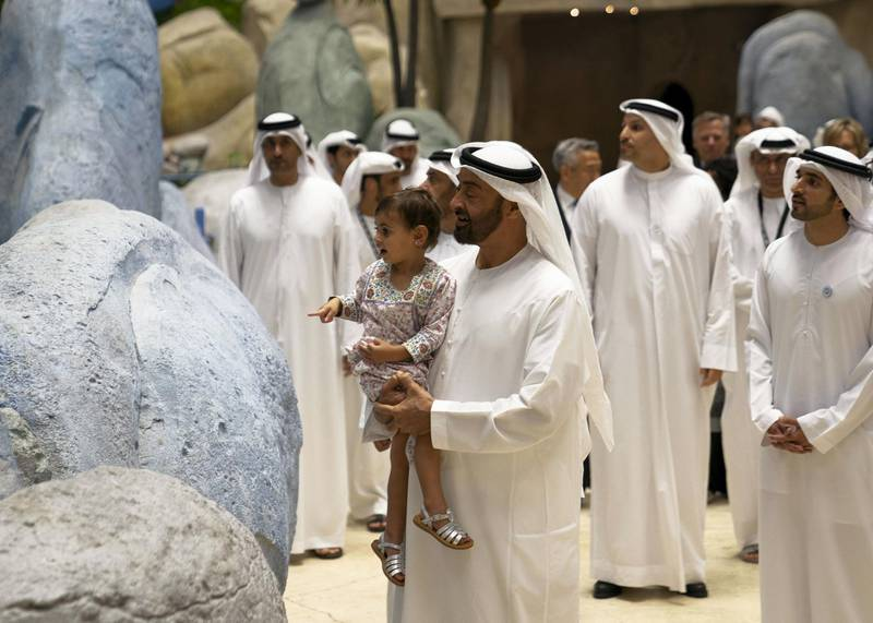 YAS ISLAND, ABU DHABI, UNITED ARAB EMIRATES - July 23, 2018: HH Sheikh Mohamed bin Zayed Al Nahyan, Crown Prince of Abu Dhabi and Deputy Supreme Commander of the UAE Armed Forces  (C) and his granddaughter HH Sheikha Salama bint Diab bin Mohamed bin Zayed Al Nahyan (L), attend the opening of Warner Bros World Abu Dhabi. Seen with HH Sheikh Hamdan bin Mohamed Al Maktoum, Crown Prince of Dubai (R) and HE Khaldoon Khalifa Al Mubarak, CEO and Managing Director Mubadala, Chairman of the Abu Dhabi Executive Affairs Authority and Abu Dhabi Executive Council Member (back).   ( Eissa Al Hammadi for The Crown Prince Court ) ---