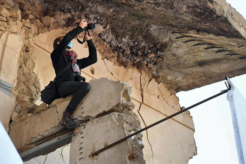 """A photojournalist uses his camera from atop a broken wall near the ruins of the Syriac Catholic Church of the Immaculate Conception (al-Tahira-l-Kubra), in the northern city of Mosul, amidst preparations ahead of the Pope's visit, on March 7, 2021.  Pope Francis, on his historic Iraq tour, visits today Christian communities that endured the brutality of the Islamic State group until the jihadists' """"caliphate"""" was defeated three years ago / AFP / Vincenzo PINTO"""