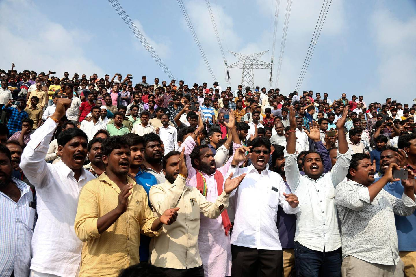 People shout slogans in favor of police and cheer them while gathering near the place where rape accused were shot in Shadnagar some 50 kilometers or 31 miles from  Hyderabad, India, Friday, Dec. 6, 2019. An Indian police official says four men accused of raping and killing a woman in southern India have been fatally shot by police. (AP Photo/Mahesh Kumar A.)