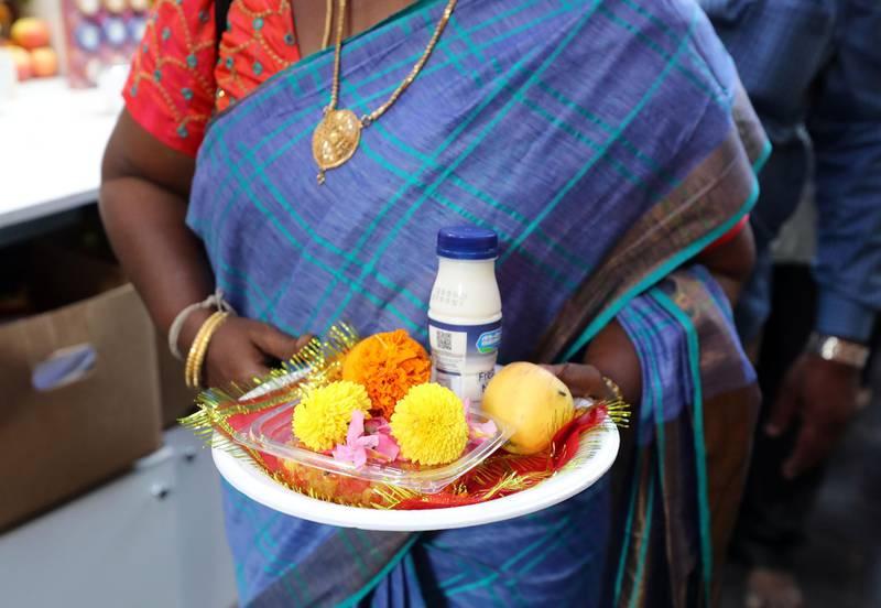 Dubai, United Arab Emirates - October 26, 2019: People bring plates with food and flowers to the Shiva Temple during Diwali in Bur Dubai. Saturday the 26th of October 2019. Bur Dubai, Dubai. Chris Whiteoak / The National