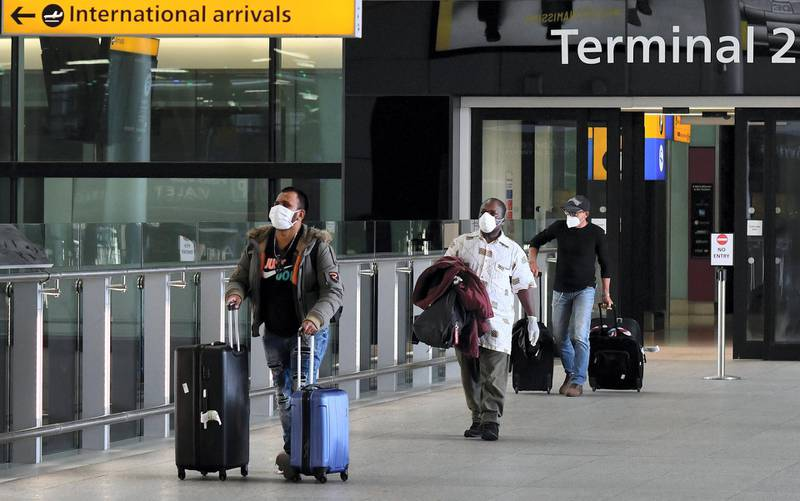 Passengers wearing PPE (personal protective equipment), including a face mask as a precautionary measure against COVID-19, walk through the arrivals hall after landing at at Terminal Two of London Heathrow Airport in west London, on May 9, 2020. - Britain could introduce a 14-day mandatory quarantine for international arrivals to stem the spread of coronavirus as part of its plan to ease the lockdown, an airline association said Saturday, sparking alarm in an industry already badly hit by the global pandemic. (Photo by JUSTIN TALLIS / AFP)