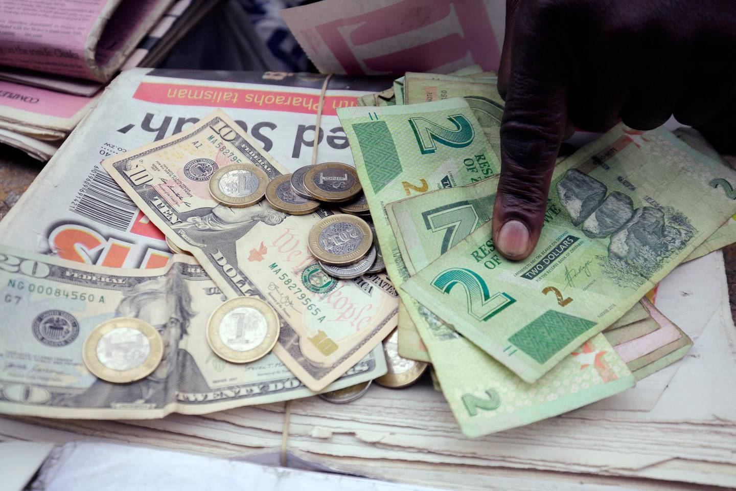 """A man counts Zimbabwean dollar notes and coins next to a ten US dollar note on the streets of Harare, Tuesday, June 25, 2019. Zimbabwe President Emmerson Mnangagwa on Tuesday praised the re-introduction of the Zimbabwe dollar as the sole legal tender in the troubled country as a """"return to normalcy."""" Zimbabwe had for 10 years used the U.S. dollar and other foreign currencies after the Zimbabwean currency was dogged by hyperinflation. (AP Photo/Tsvangirayi Mukwazhi)"""