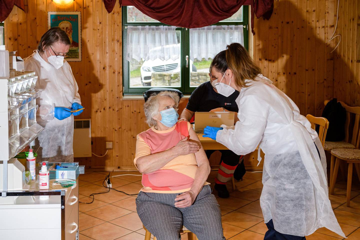 NAUMBURG, GERMANY - MARCH 01: Nurse Susann Wolter (R) vaccinates Renate Bauer (C), 82, with the Pfizer-BioNTech vaccine in an old clubhouse during the novel coronavirus pandemic in Seidewitz on March 1, 2021 near Naumburg, Germany. So far approximately 4.4% of Germany's population has received the first dose of a Covid-19 vaccine. (Photo by Jens Schlueter/Getty Images)