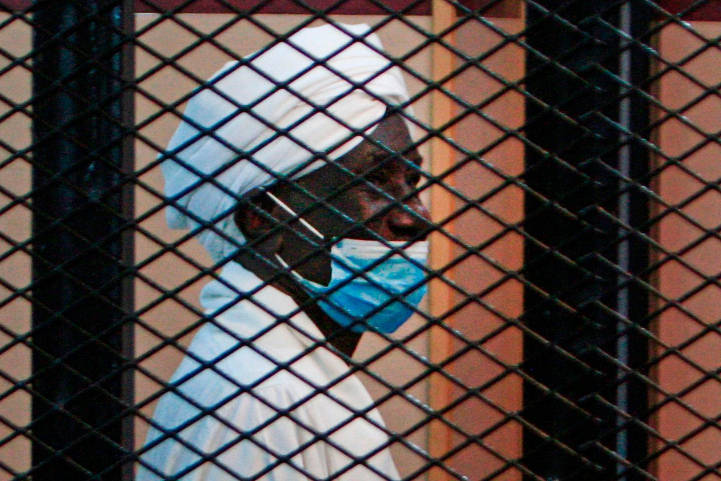 CORRECTION / Sudan's former vice presidents Ali Osman Taha is pictured behind the bars during the trial of ousted president Omar al-Bashir, along with others at a courthouse in the Sudanese capital Khartoum, on August 25, 2020.  The trial of Sudan's ousted president Omar al-Bashir, on charges related to the coup that brought him to power in 1989, was adjourned to September 1, the judge said.  / AFP / Ebrahim HAMID