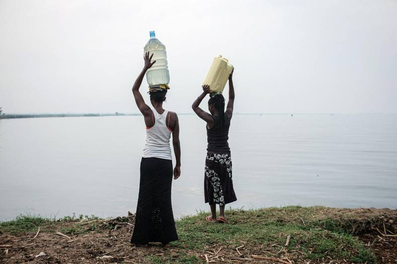 Women hold containers filled with water above their heads after fetching water from the Nile river near the Kisomere village in western Uganda, on January 28, 2020. - When exploitable crude oil deposits were discovered in 2006 in the Lake Albert region, Uganda began to imagine itself as a new oil Eldorado. But 14 years later, the mirage has faded, and it is still waiting to extract its first drops of black gold. This discovery had raised wild hopes in a country where 21% of the population lives in extreme poverty. The Ugandan government saw the prospect of earning at least $1.5 billion a year and increasing its GDP per capita from $630 to over $1,000. (Photo by Yasuyoshi CHIBA / AFP)