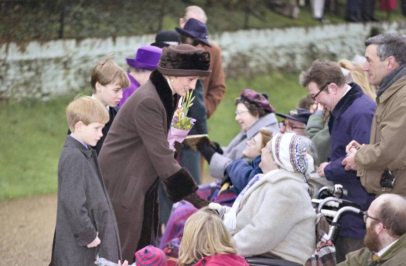 British Royals Prince Harry, Prince William and Diana, Princess of Wales (1961-1997), wearing a brown coat with black trim and a matching winter hat, greeting wellwishers as they attend the Christmas Day service at St Mary Magdalene Church on the Sandringham Estate in Sandringham, Norfolk, England, 25th December 1994. Partially obscured in the background are Queen Elizabeth II and Prince Philip. (Photo by Princess Diana Archive/Hulton Archive/Getty Images)