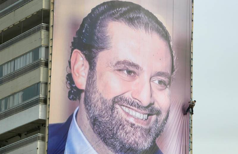A worker is seen fixing a huge banner depicting Lebanese prime minister Saad al-Hariri, who resigned a fortnight ago during a visit to Saudi Arabia, in the southern city of Sidon, Lebanon, November 18, 2017. REUTERS/Ali Hashisho