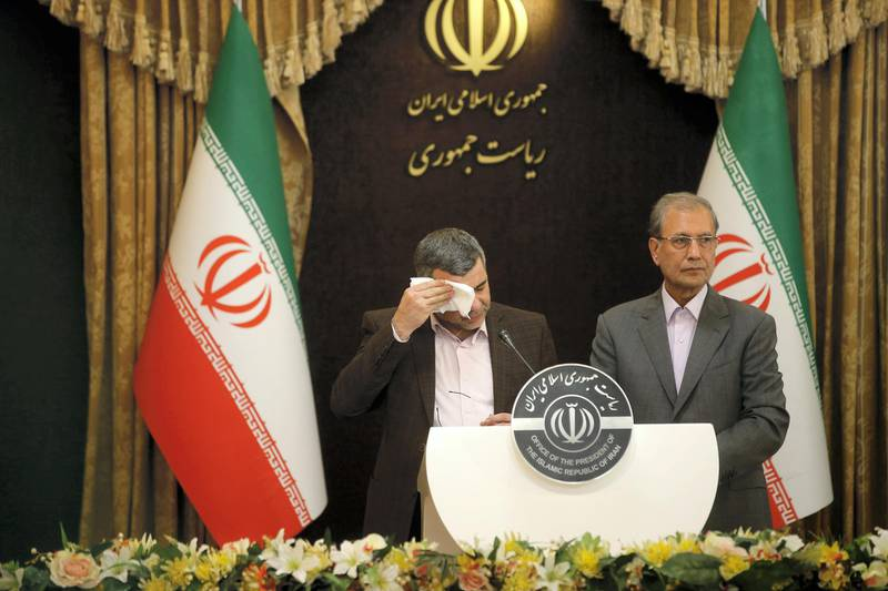 Iranian Deputy Health Minister Iraj Harirchi (L) wipes the sweat off his face, during a press conference with the Islamic republic's government spokesman Ali Rabiei in the capital Tehran on February 24, 2020. - Iran's deputy health minister confirmed on February 25, that he has tested positive for the novel coronavirus, amid a major outbreak in the Islamic republic. Harirchi coughed occasionally and appeared to be sweating during the press conference with Rabiei in Tehran. (Photo by Mehdi BOLOURIAN / FARS NEWS / AFP)