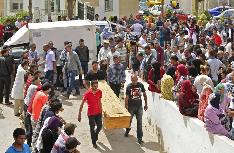 People wait to receive the bodies of loved ones in the Tunisian town of Sfax on June 4, 2018 after more than 50 migrants drowned in the Mediterranean on the previous day, the majority off the coasts of Tunisia and Turkey. Tunisians and migrants regularly try to cross the Mediterranean to seek a better future in Europe, with 120 mainly Tunisians rescued by their navy in March after trying to reach Italy.     / AFP / Sofiene HAMDAOUI