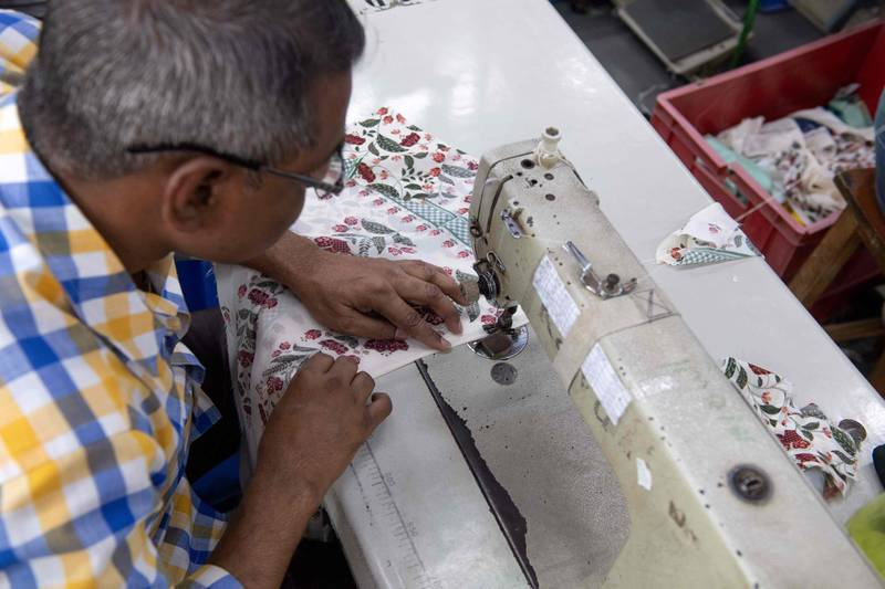 In this photo taken on February 14, 2020, a man works on a sewing machine at the factory of fashion designer Anita Dongre on the outskirts of Mumbai. With stores in India and New York, multiple clothing brands and a global celebrity following, fashion designer Anita Dongre is a feminist powerhouse in a male-dominated industry. But her true ambition is to create an environmentally sustainable company, she says. - TO GO WITH Women-activism-India-fashion-economy-environment,INTERVIEW by Ammu Kannampilly  / AFP / Laurène Becquart / TO GO WITH Women-activism-India-fashion-economy-environment,INTERVIEW by Ammu Kannampilly