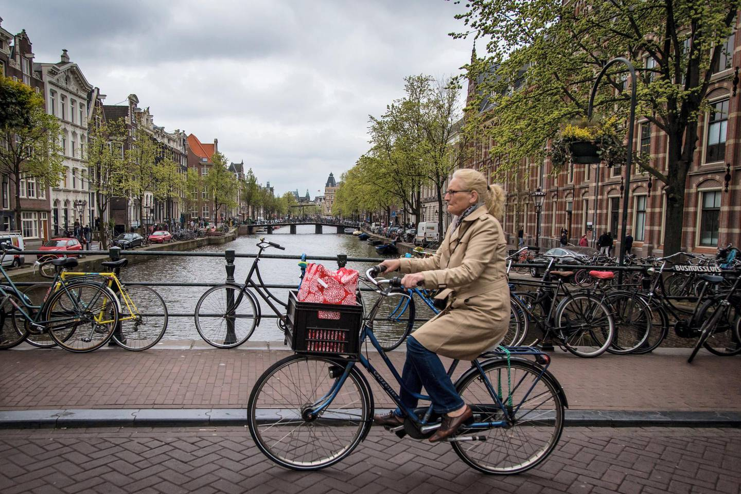 View of a canal in Amsterdam with a woman on a bicycle on April 12, 2017. (Photo by Aurore Belot / AFP)