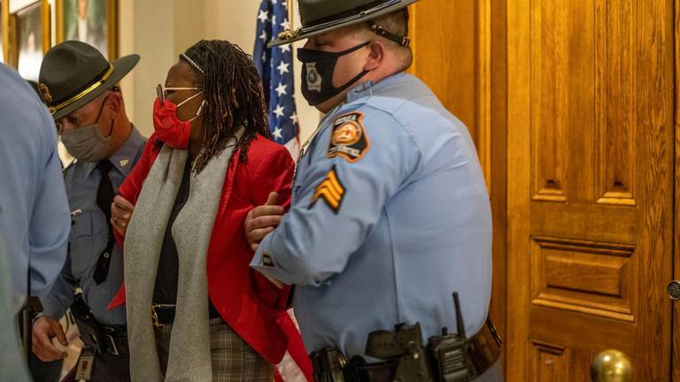 An image that illustrates this article Georgia politician arrested as governor signs sweeping voting law