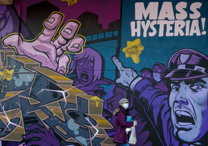 """A pedestrian, wearing a protective mask, walks past a street art mural, depicting """"Mass Hysteria"""" related to the Covid-19 pandemic, in Birmingham, U.K., on Monday, April 6, 2020. Telecom masts that enable the next generation of wireless communication were set on fire in the U.K. in recent days, apparently by people motivated by a theory that the tech helps spread the coronavirus.Photographer: Darren Staples/Bloomberg"""