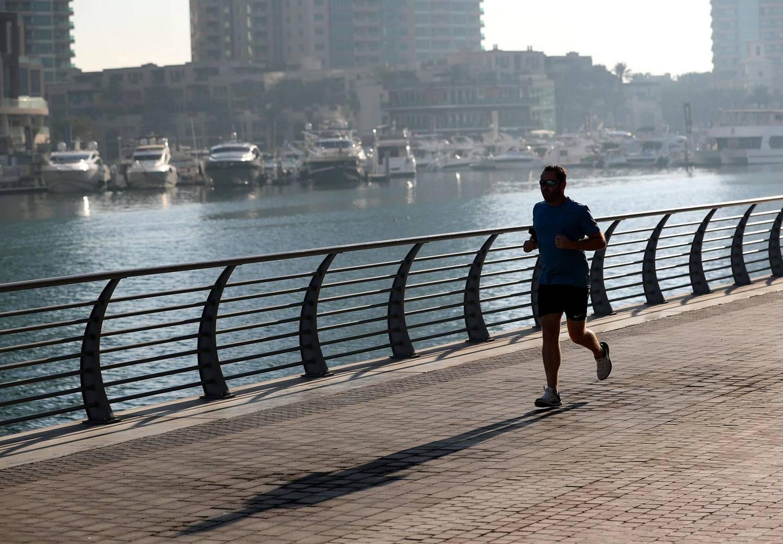 Dubai, United Arab Emirates - December 26th, 2017: Standalone. A man jogs round the marina. Tuesday, January 2nd, 2018 at Marina, Dubai. Chris Whiteoak / The National