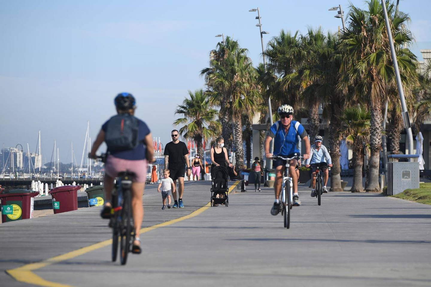 People walk and cycle at St. Kilda Beach in Melbourne, Australia, Wednesday, Feb. 17, 2021. Melbourne, Australia's second-largest city, will relax its third lockdown restrictions after authorities contained the spread of a COVID-19 cluster centered on hotel quarantine. (Erik Anderson/AAP Image via AP)