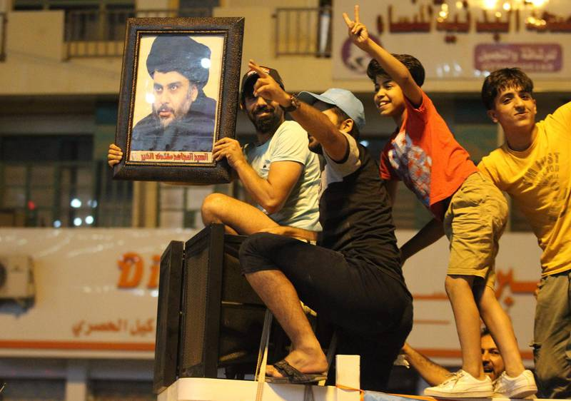 An Iraqi man celebrates with a picture of Shiite cleric Muqtada Sadr during the general election in Baghdad on May 14, 2018.  The race to become Iraq's next prime minister appeared wide open as two outsider alliances looked to be in the lead after the first elections since the defeat of the Islamic State group. / AFP / AHMAD AL-RUBAYE