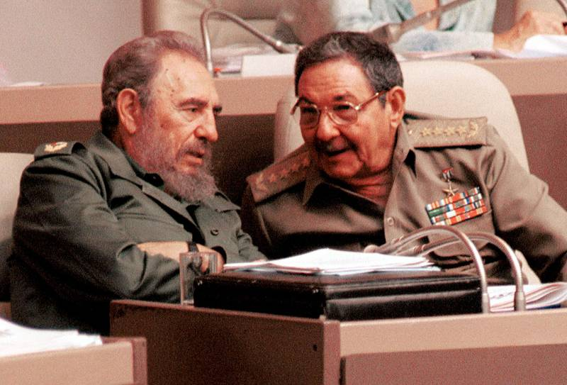 """392855 03: Cuban President Fidel Castro, left, and his brother Raul Castro, speak to each other August 3, 2001 during a session of the National Assembly legislature in Havana. The parliament condemned U.S. President George W. Bush''s """"cruel"""" policies on Cuba, and called for the release of five Cuban agents jailed in Miami on spy-related charges. (Photo by Jorge Rey/Getty Images)"""