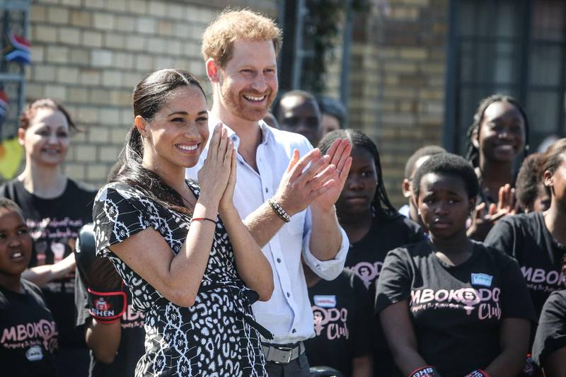 """Prince Harry, Duke of Sussex and Meghan, Duchess of Sussex arrive for a visit to """"Justice  desk"""", an NGO in the township of Nyanga in Cape Town, as they begin their tour of the region on September 23, 2019. Britain's Prince Harry and his wife Meghan arrived in South Africa on September 23, launching their first official family visit in the coastal city of Cape Town. The 10-day trip began with an education workshop in Nyanga, a township crippled by gang violence and crime that sits on the outskirts of the city. / AFP / POOL / POOL / Betram MALGAS"""